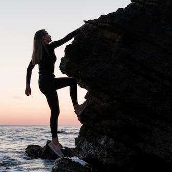 Mulher de lado escalando uma rocha perto do oceano