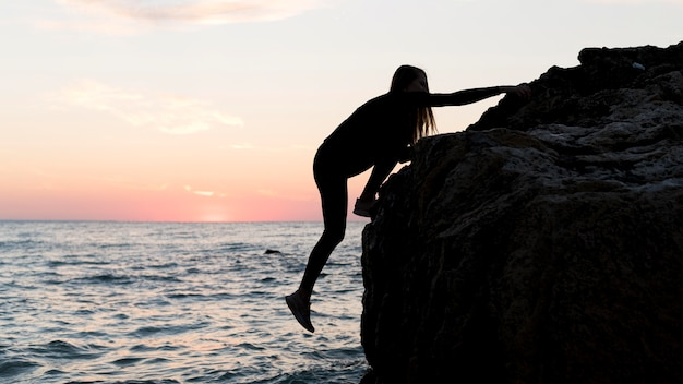 Mulher de lado escalando uma rocha