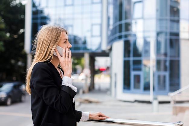 Mulher de lado falando ao telefone