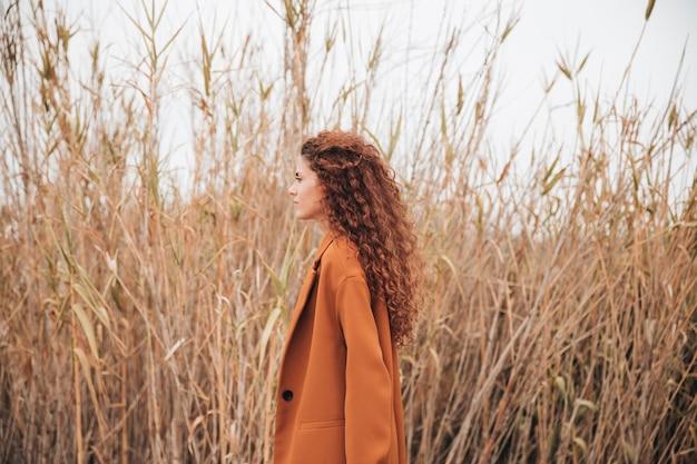 Mulher de lado no campo de trigo, olhando para longe