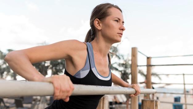 Mulher de lado se exercitando em roupas esportivas