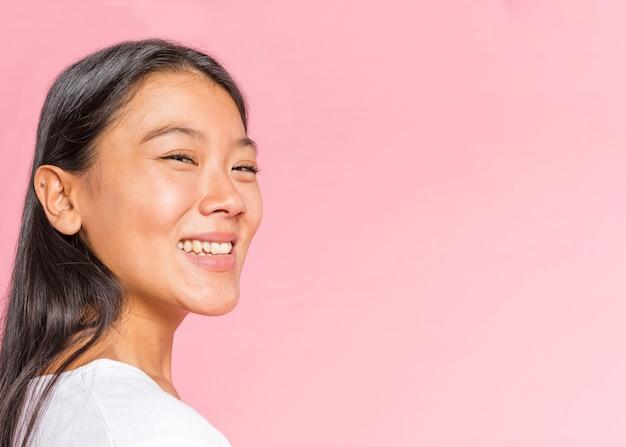 Mulher de lado sorrindo para a câmera