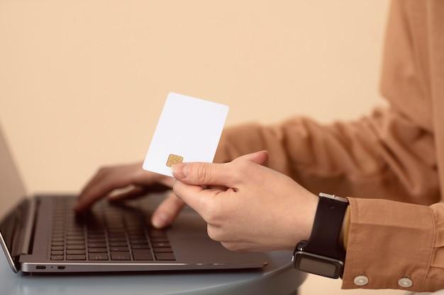 Mulher de lado usando laptop e cartão de compras