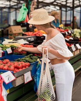 Mulher de lado usando sacola orgânica para vegetais