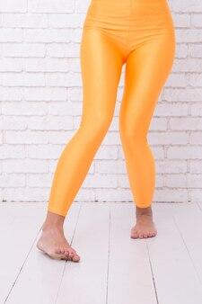 Mulher de legging laranja nas pernas. moda desgaste do esporte. laranja. praticando no estúdio de balé. dançando balé posição dos pés. uma vida cheia de diversão. ficando louco. jogando duro. diversão em movimento.