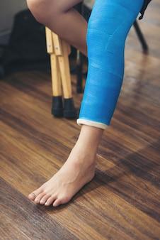 Mulher de lesão com perna splint sentado e muletas de madeira no hospital