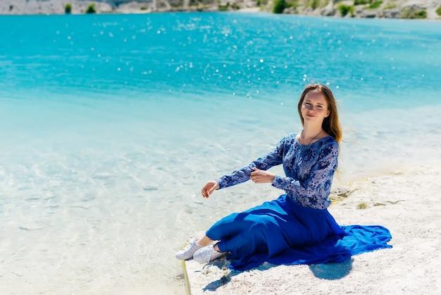 Mulher de liberdade em êxtase de felicidade livre na praia. sorrindo, modelo feminino multicultural feliz com vestido azul de verão, curtindo a natureza serena do oceano durante a viagem de férias ao ar livre.