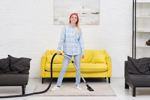Mulher de limpeza com aspirador