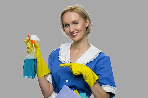 Mulher de limpeza de uniforme apresentando detergente. governanta bonita mostrando o frasco de química para limpeza. anúncio de spray mais limpo.