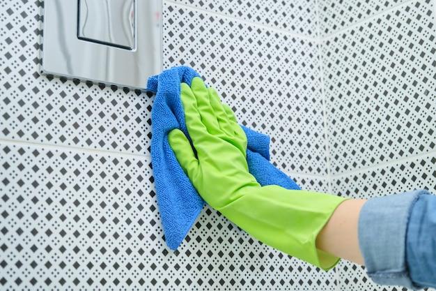 Mulher de limpeza e polimento de cromo banheiro botão na parede de azulejos