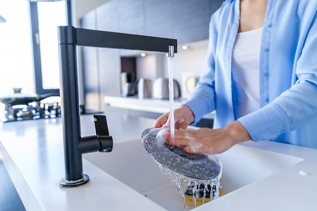 Mulher de limpeza lavar a louça durante o trabalho doméstico