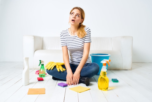 Mulher de limpeza perto da sala do sofá, limpeza de luvas de proteção. foto de alta qualidade