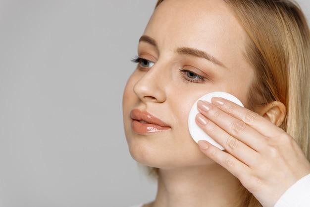 Mulher de limpeza (remoção de maquiagem) o rosto com almofada de algodão