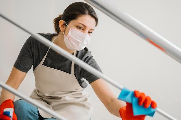 Mulher de limpeza usando máscara médica