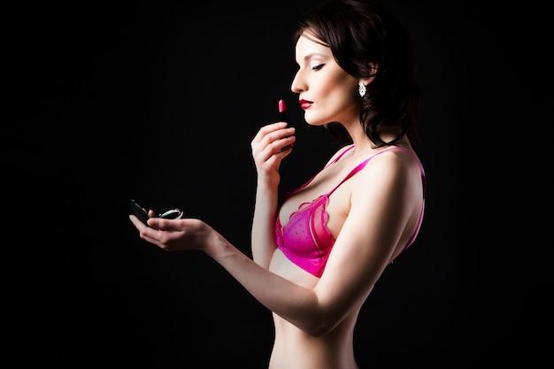 Mulher de lingerie detém um batom vermelho sobre um fundo escuro.