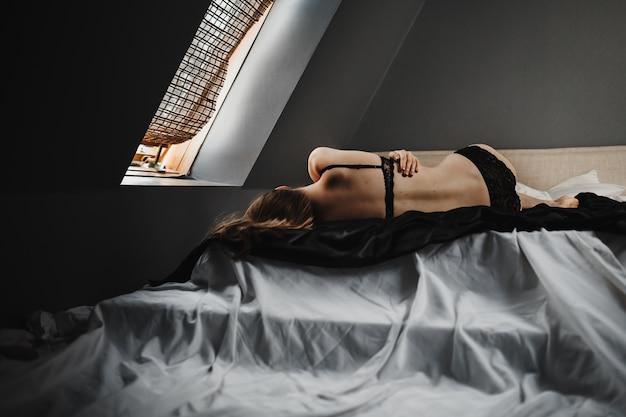 Mulher de lingerie preta encontra-se na cama cinza antes da janela