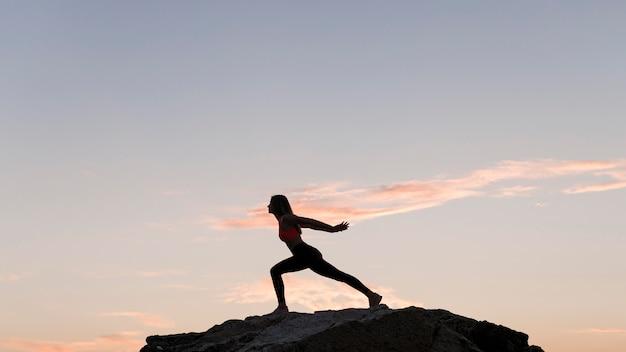 Mulher de longo alcance em uma posição esportiva em uma rocha com espaço de cópia