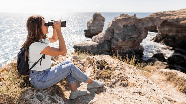 Mulher de longo alcance usando binóculos com espaço de cópia
