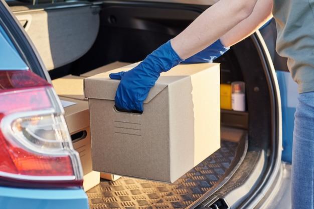 Mulher de luvas, colocando uma caixa na mala do carro