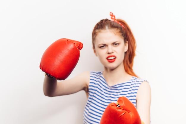 Mulher de luvas de boxe e camiseta listrada gritando o estresse da agressão