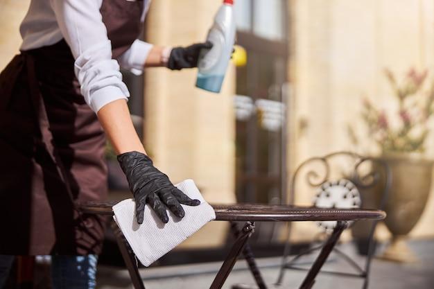 Mulher de luvas preparando café para abrir o convidado