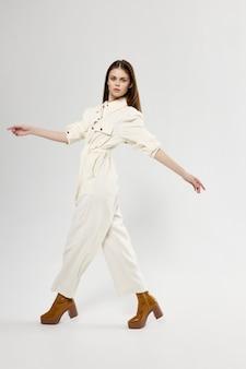Mulher de macacão branco sobre um fundo claro roupas da moda sapatos