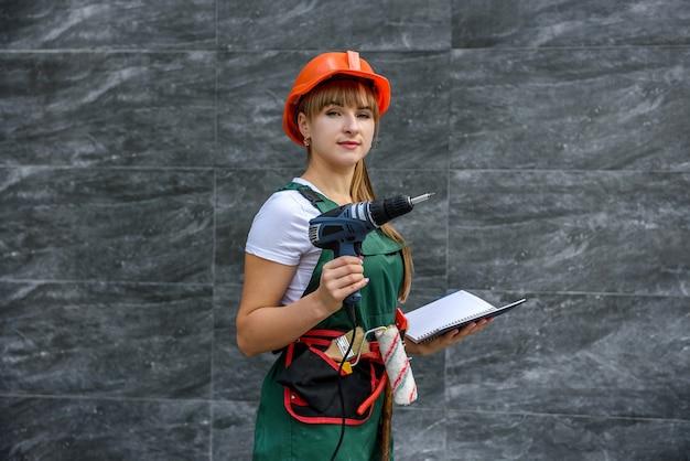 Mulher de macacão de proteção e capacete segurando uma chave de fenda e um diário em abstrato