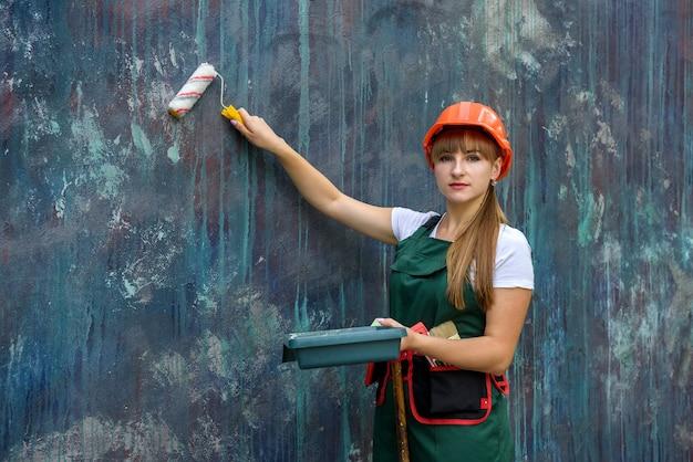 Mulher de macacão e capacete pintando parede com rolo
