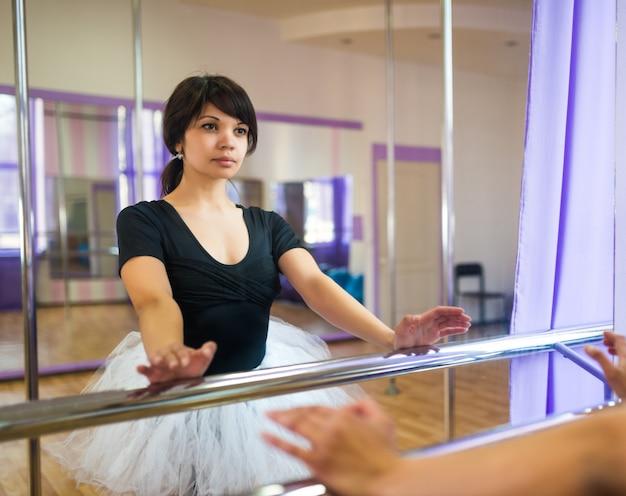Mulher de macacão preto e tutu branco fazendo aula de balé perto da máquina de balé