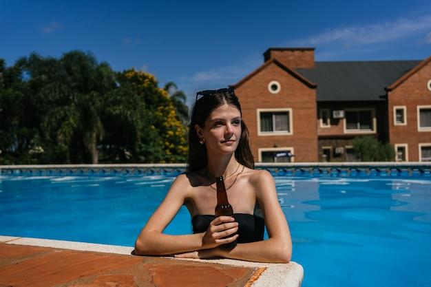Mulher de maiô está bebendo cerveja na piscina.