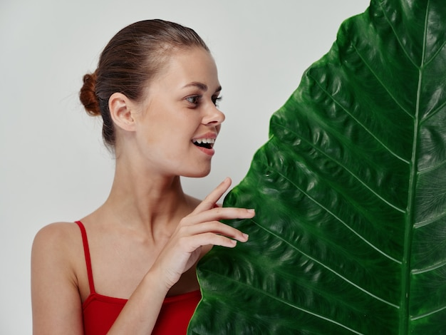 Mulher de maiô olhando para a pele clara de folha de palmeira verde