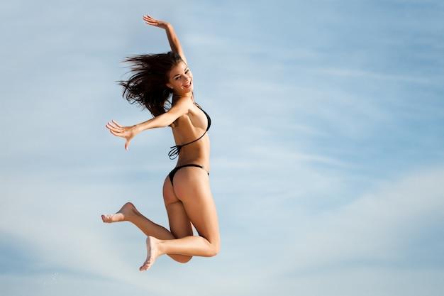 Mulher de maiô preto, saltando alto