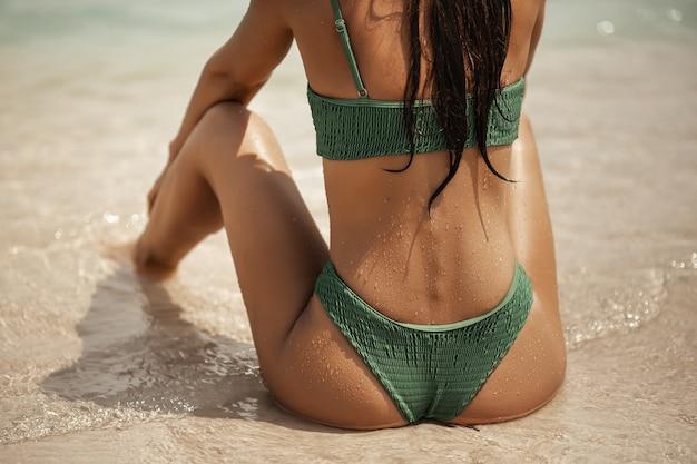 Mulher de maiô sentada na praia e olhando para o mar. vista de perto da parte de trás de um deslumbrante
