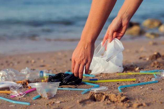 Mulher de mão pegando uma garrafa de plástico limpando na praia, conceito voluntário