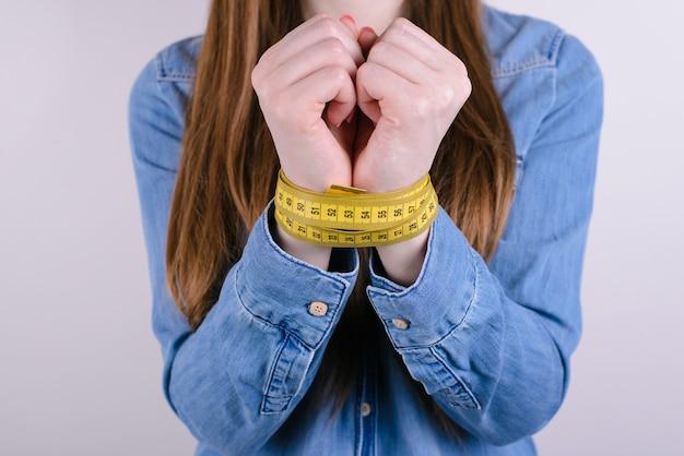 Mulher de mãos amarradas com centímetro amarelo isolado