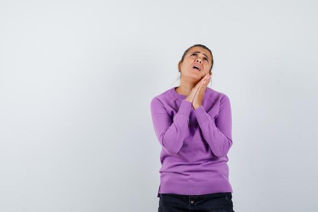 Mulher de mãos dadas em gesto de oração em blusa de lã e parecendo indefesa