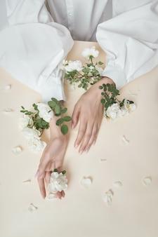 Mulher de mãos de beleza com flores rosas está em cima da mesa. cosmético natural para cuidados com a pele das mãos. maquiagem fashion