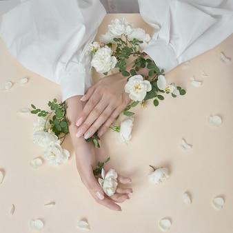 Mulher de mãos de beleza com flores rosas está na mesa. cosmético natural para cuidados com a pele das mãos. maquiagem da moda