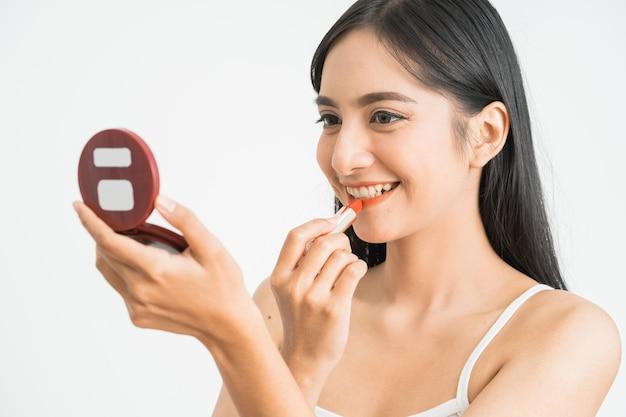 Mulher de maquiagem batom colocando protetor labial. menina asiática de beleza aplicando cosméticos, preparando-se e olhando-se no espelho sorrindo feliz. modelo caucasiano asiático multiétnico.