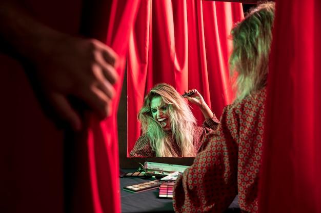Mulher de maquiagem para o halloween brincando na frente de um espelho