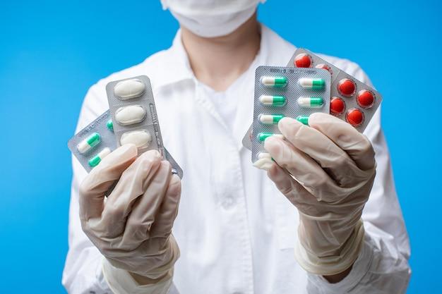 Mulher de máscara de segurança segurando diferentes comprimidos médicos posando