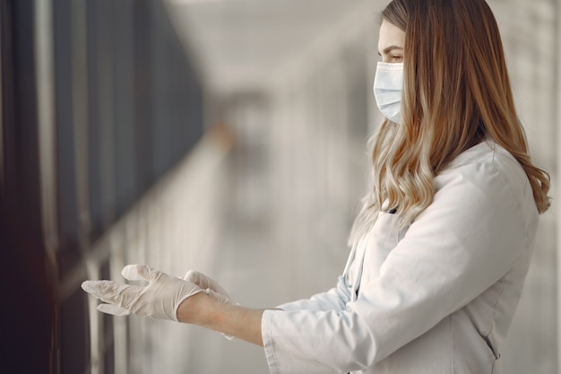 Mulher de máscara e uniforme veste luvas