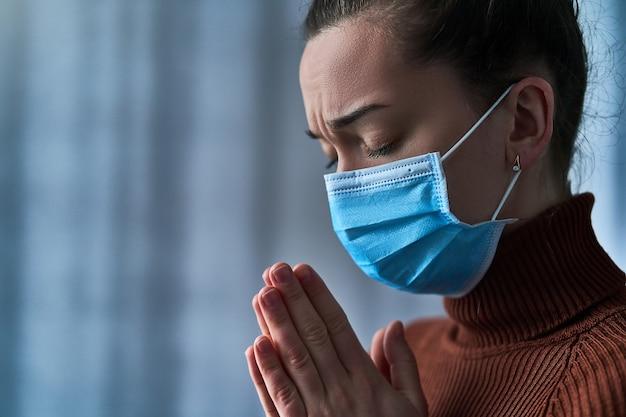 Mulher de máscara protetora com os olhos fechados e mãos a rezar, pede a deus cura e recuperação durante a doença