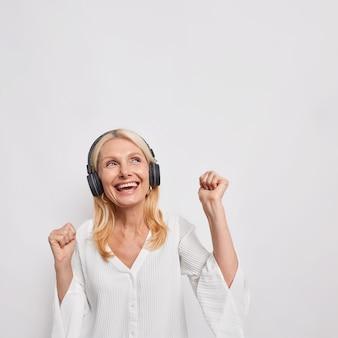 Mulher de meia-idade alegre dança despreocupada e se diverte mantém os braços levantados sorrisos amplamente usa fones de ouvido estéreo sem fio usa blusa isolada sobre a parede branca
