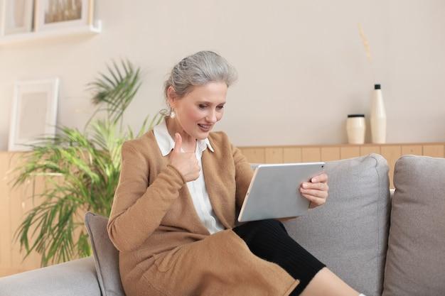 Mulher de meia idade alegre sentada no sofá, usando aplicativos de tablet de computador, olhando para a tela, lendo boas notícias na rede social, fazendo compras ou conversando online.