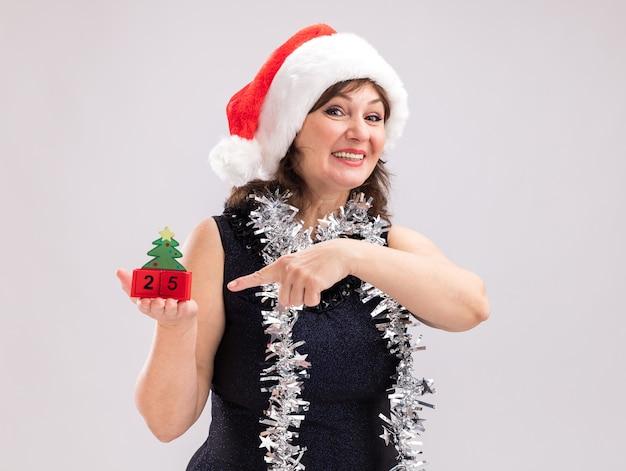 Mulher de meia-idade alegre usando chapéu de papai noel e guirlanda de ouropel no pescoço segurando e apontando para o brinquedo da árvore de natal com data olhando para a câmera, isolada no fundo branco