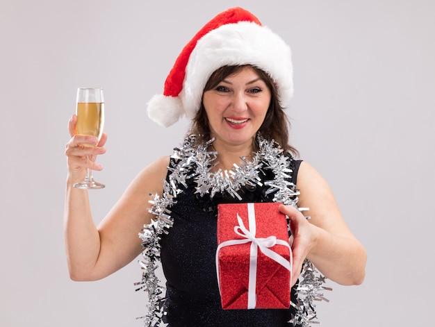 Mulher de meia-idade alegre usando chapéu de papai noel e guirlanda de ouropel no pescoço segurando uma taça de champanhe estendendo o pacote de presente em direção à câmera, olhando para a câmera isolada no fundo branco