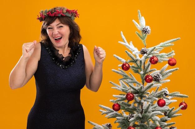 Mulher de meia-idade alegre usando coroa de natal na cabeça e guirlanda de ouropel em volta do pescoço, perto da árvore de natal decorada