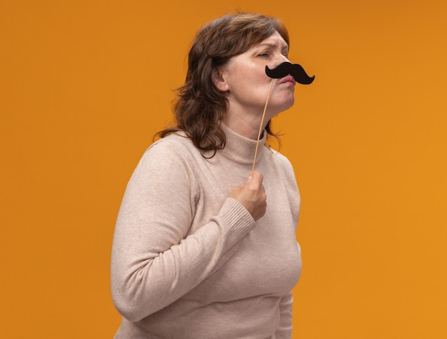 Mulher de meia-idade alegre, vestindo uma blusa de gola alta bege, usando óculos e segurando um bigode em frente ao rosto, de pé sobre uma parede laranja