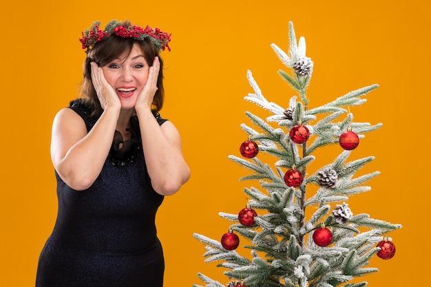 Mulher de meia-idade animada com uma coroa de natal na cabeça e uma guirlanda de ouropel ao redor do pescoço, perto da árvore de natal decorada